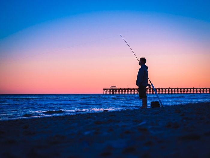 Surface level view of silhouette man fishing on shore against clear sky