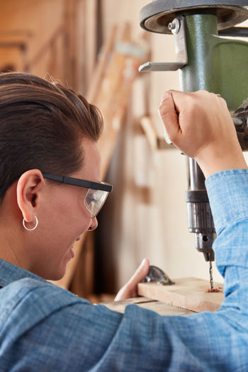 Close-up of smiling carpenter using drill at workshop
