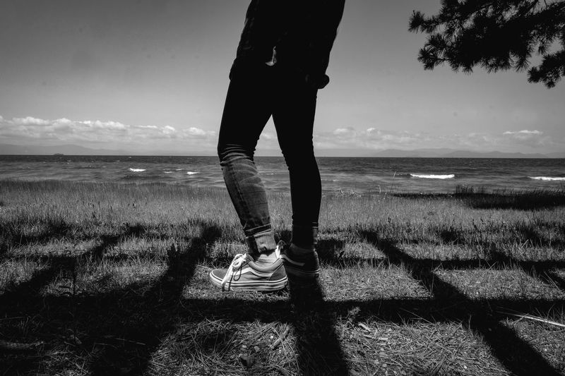 Monochrome monochrome photography Sea Water Sky Beach Land Horizon One Person Nature Horizon Over Water Low Section Sunlight Standing Body Part Human Leg Scenics - Nature Shadow Human Body Part Real People Day Outdoors