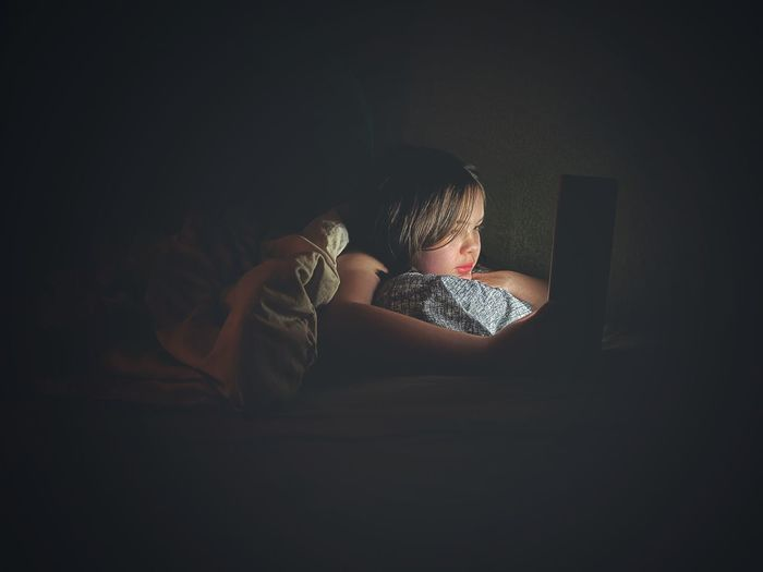 Rear view of girl using laptop on bed