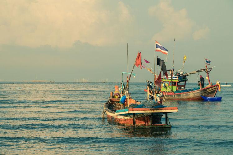 Fishing boat sailing in sea against sky