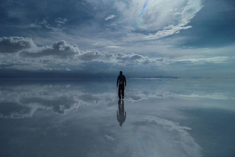 Man Wading In Sea Against Sky