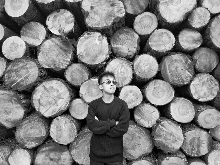 Man Standing Against Stack On Logs
