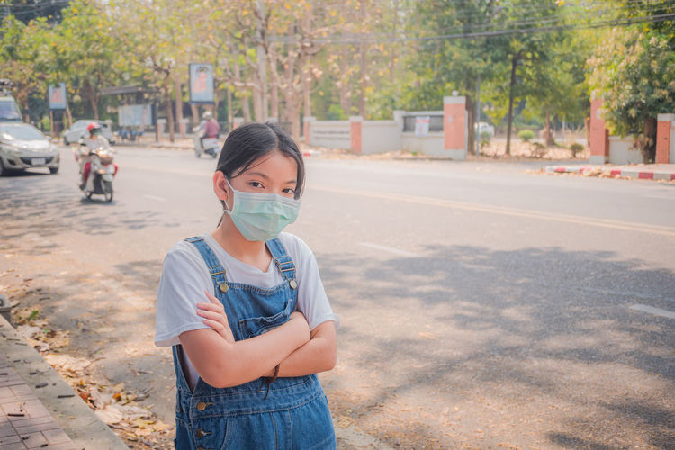Coronavirus and air pollution pm2.5 concept. young girl wearing face mask protective for spreading.
