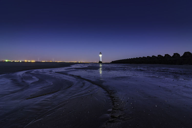 Lighthouse by sea against clear sky at night