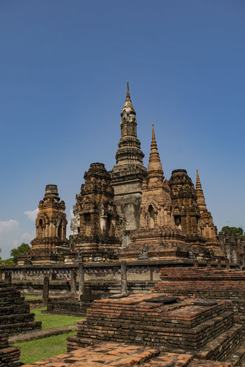 Low angle view of ruined pagoda against clear blue sky