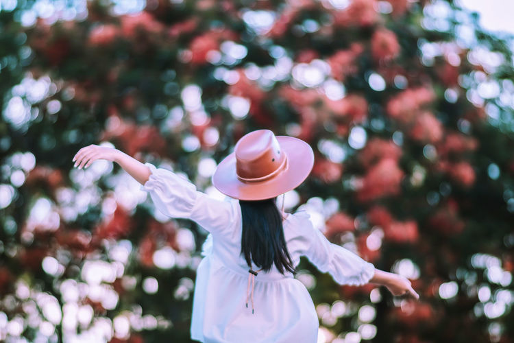 Love Bokeh .Young woman are flying in the flowers. Celebration Arms Raised Bokeh Bokeh Photography Casual Clothing Child Clothing Day Focus On Foreground Hairstyle Hat Human Arm Human Limb Leisure Activity Lifestyles Nature One Person Plant Portrait Real People Rear View Standing Three Quarter Length Tree Women