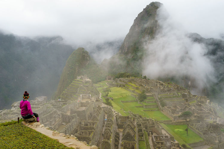 Rear view of woman sitting at machu picchu against sky