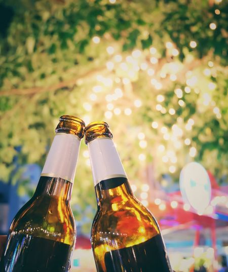 Close-Up Of Beer Bottles Against Illuminated Trees