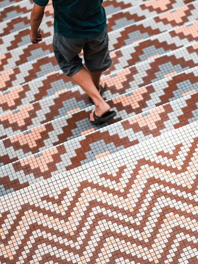 A boy walking down a classic design mosaic steps