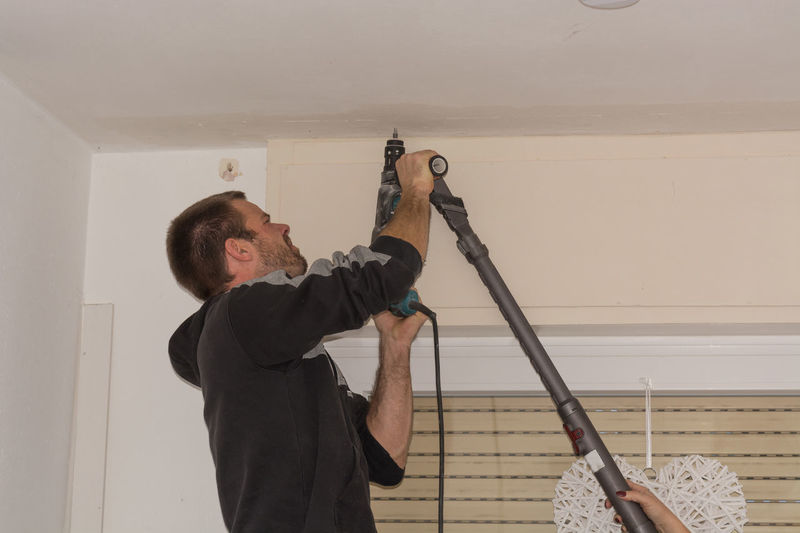 The man drills a hole in the ceiling before mounting a curtain rod One Person Real People Indoors  Holding Men Standing Home Interior Wall - Building Feature DIY Side View Lifestyles Young Adult Adult Waist Up Home Improvement Young Men Architecture Males  Ladder Ceiling #NotYourCliche Love Letter Humanity Meets Technology