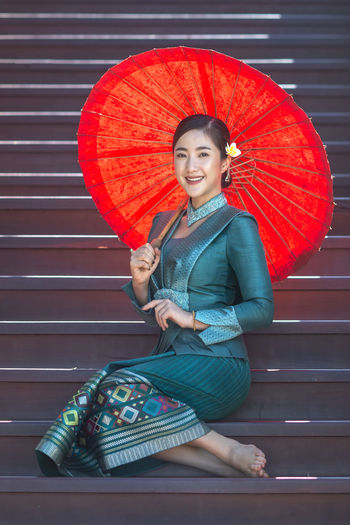 Portrait of a smiling young woman holding umbrella