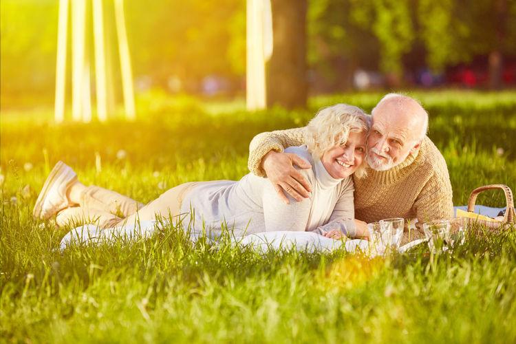 Portrait Of Smiling Senior Couple Lying On Field