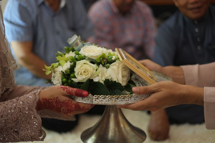 Cropped Hands Of Wedding Couple Holding Bouquet