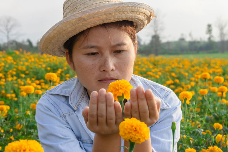 Marigold Portrait Flower Marigold Flower Farmer Selective Focus Lifestyles Outdoors Nature Plant Leisure Activity Care Check Hat One Person Front View Yellow Freshness Real People Holding Casual Clothing Headshot Clothing Flowering Plant Fragility Growth Field