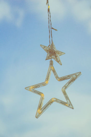 Low angle view of christmas decoration hanging against sky