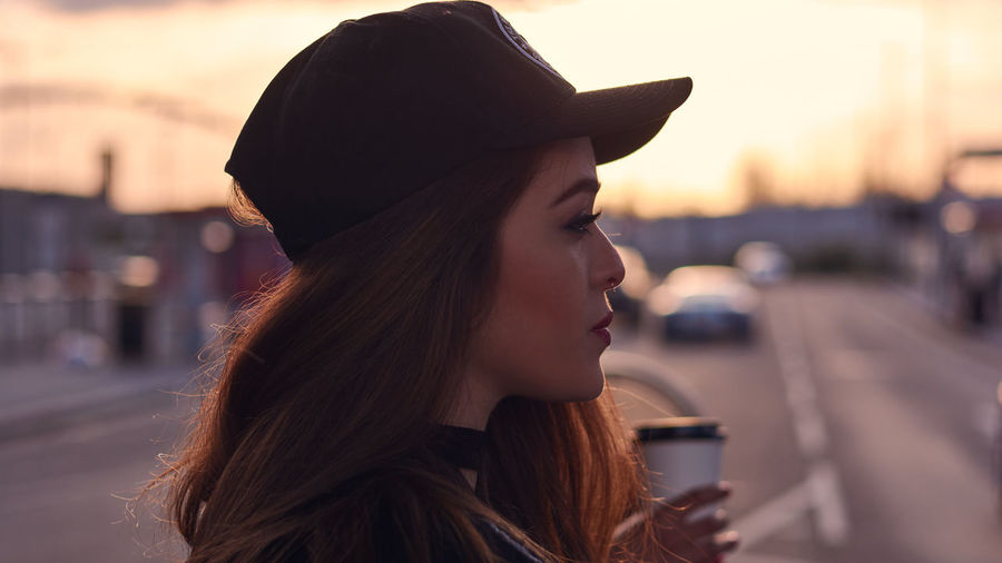 Close-up of woman on city street at sunrise
