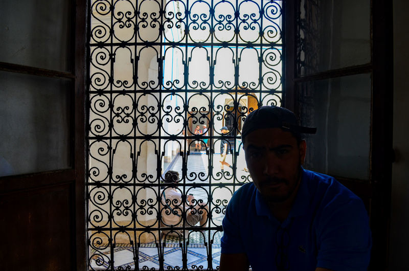 Portrait of man looking through window in building