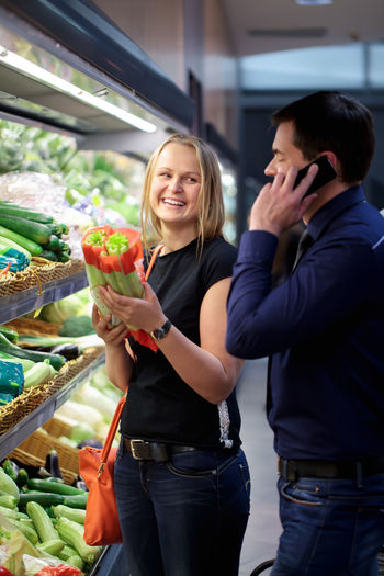 Happy young couple shopping at greengrocer shop
