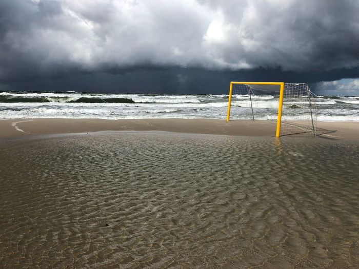Goal post at beach against storm clouds