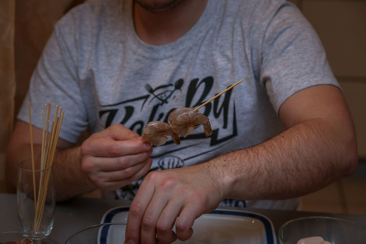 Midsection of man holding hands at home