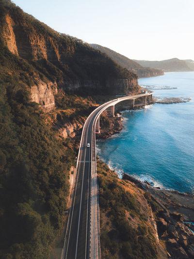 Bridge by sea against clear sky