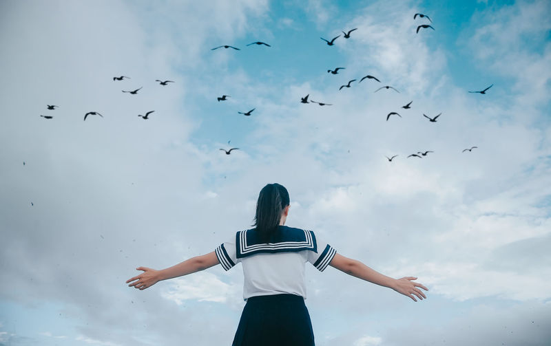 Low angle view of birds flying over teenage girl against cloudy sky