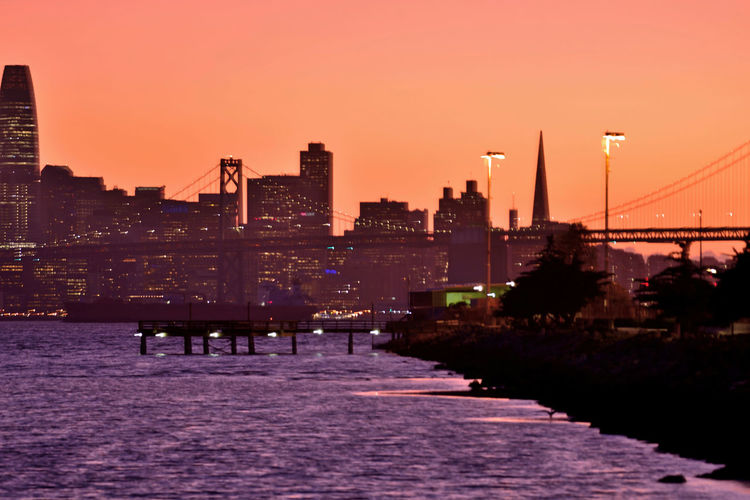 Silhouette bridge over river by buildings against sky during sunset