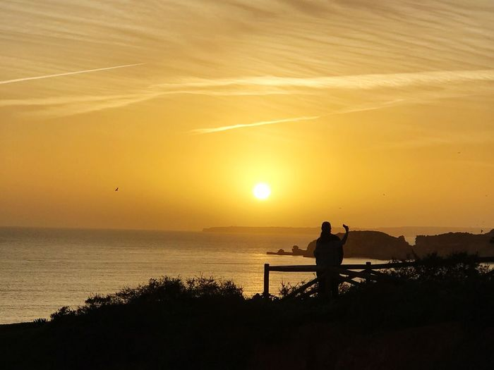 Silhouette man standing at observation point by sea against sky during sunset