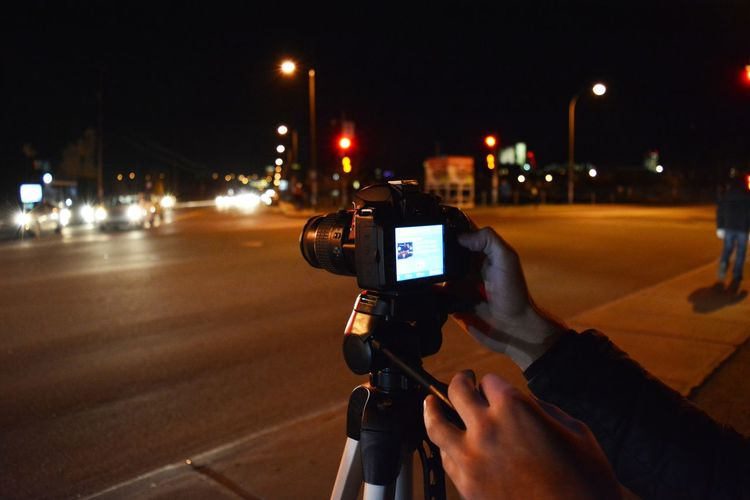Midsection of man photographing illuminated on road at night