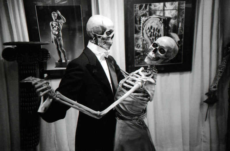 Skeletons dancing against curtain