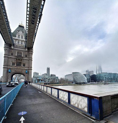 Bridge over road by buildings in city against sky