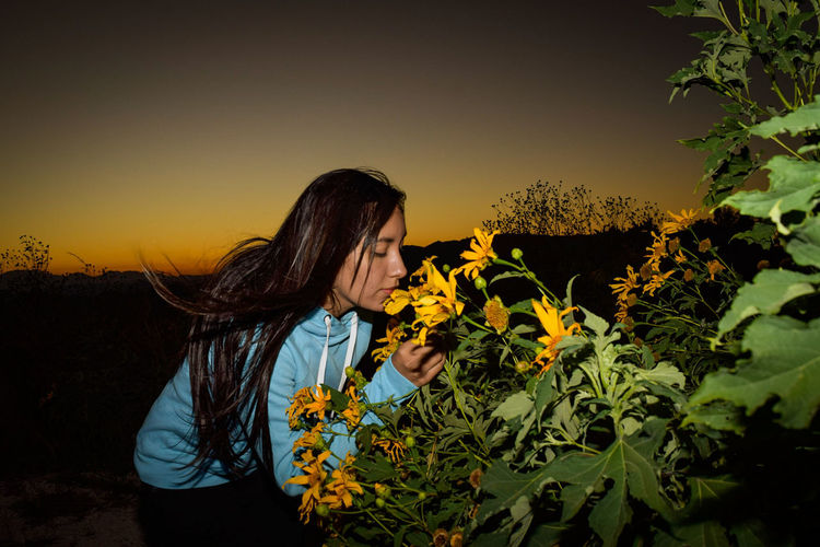 Woman with yellow flowers against sky during sunset