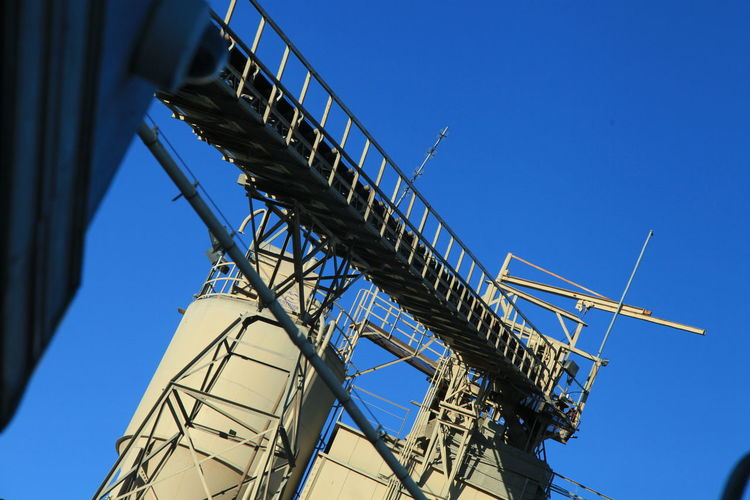 Low Angle View Of Large Machines Against Clear Blue Sky