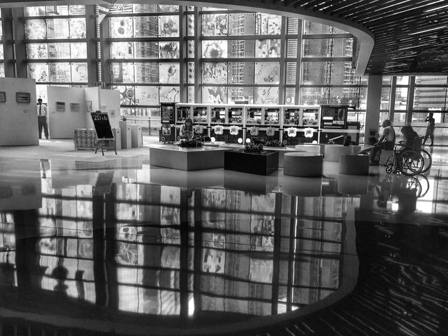 In a mall Streetphotography Streetphoto_bw Monochrome Photography Indoors  Shopping Mall Embrace Urban Life Reflection Windows Inverted Images Curve Light And Darkness  Modern Architecture Wheelchair Art Fair Shapes And Forms Light And Shadow