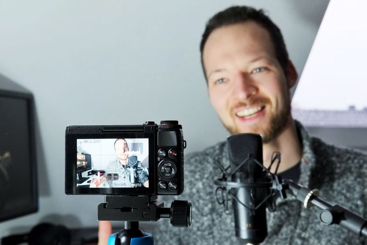 digital camera display of filming a podcaster filmmaker Content Creator Compact Camera Podast Filmmaking Technology Smiling Portrait Young Men Young Adult Photographic Equipment Headshot Front View Digital Camera