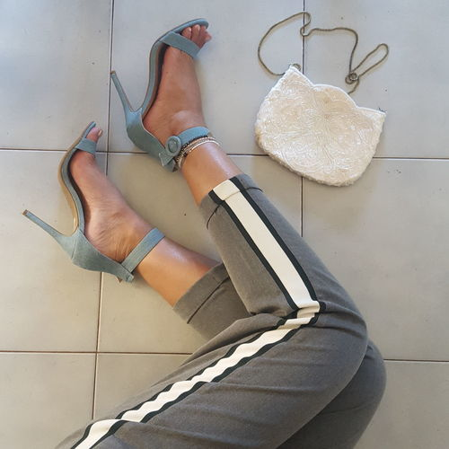 Low section of woman wearing high heels on tiled floor