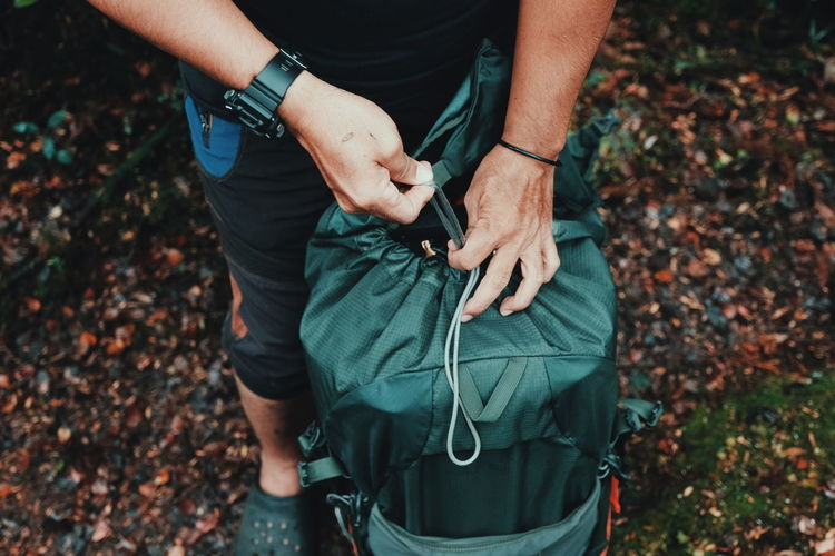Low section of man with luggage in forest during autumn