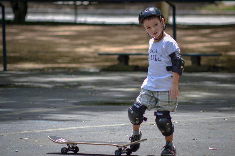 Full length of boy skateboarding on road