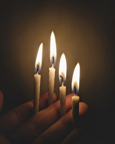 Close-up of candles burning in darkroom