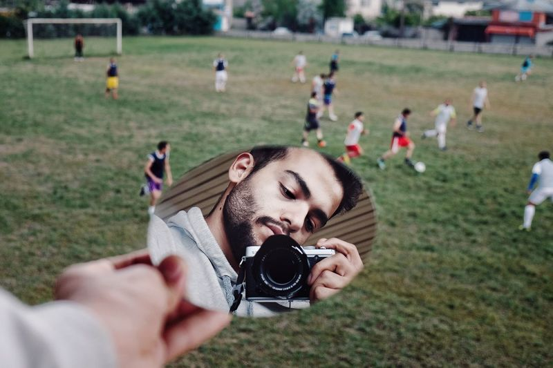 Reflection of man holding camera in mirror with boys playing soccer on field