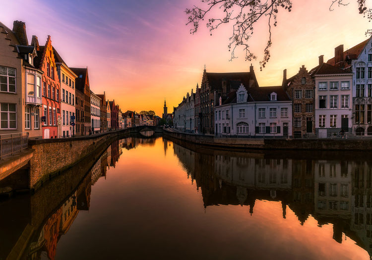 Reflection of buildings on canal in city during sunset