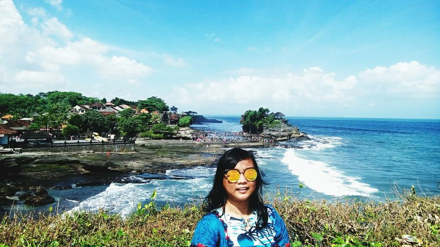 Portrait of woman wearing sunglasses while standing by sea against cloudy sky at uluwatu temple