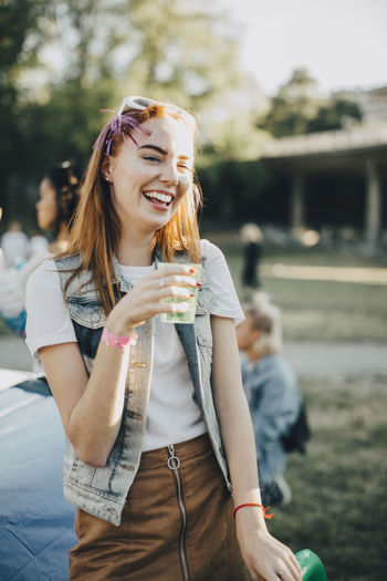 Young woman holding ice cream standing outdoors