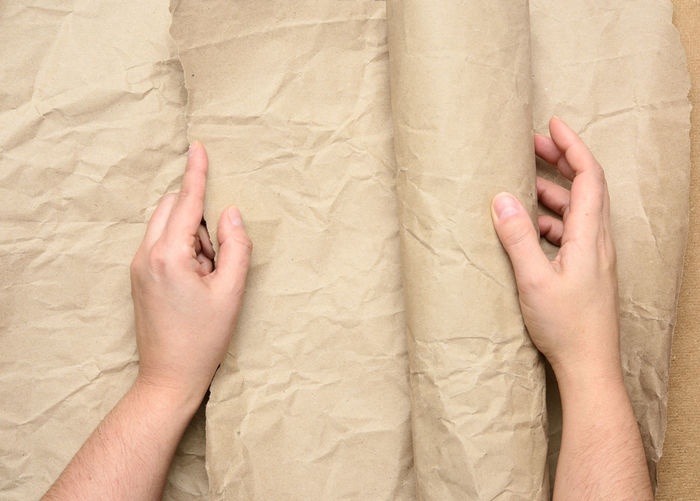 Cropped hand of man holding wrapping paper