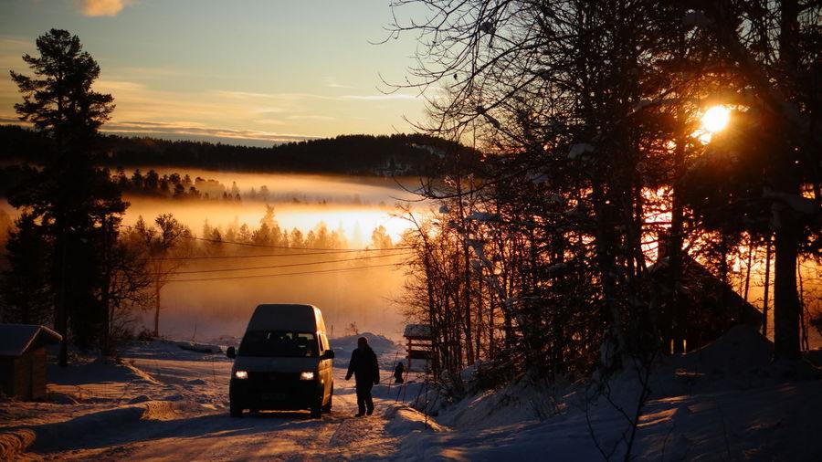 Car on snowcapped landscape at dusk