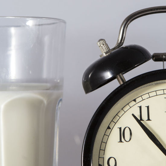 Close-up of milk by alarm against white background