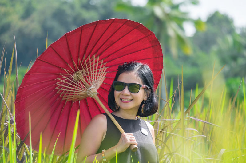 Adult Field Rice Paddy Woman Beautiful Woman Day Greenery Happiness Leisure Activity Lifestyles Nature One Person Outdoors Paddy Field People Portrait Real People Red Smiling Sunglasses Tree Umbrella