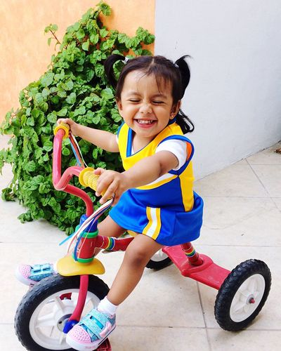 Full length of happy girl riding tricycle