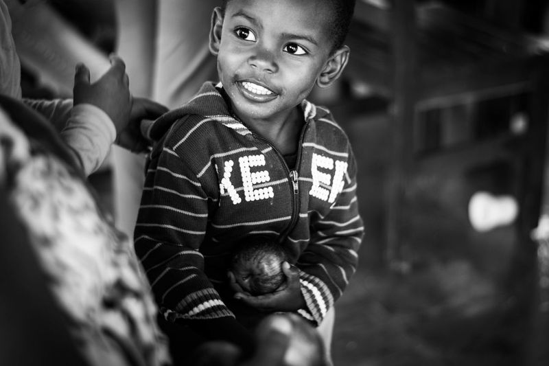 Child Smiling Black And White Boys Casual Clothing Child Child Smiling Childhood Front View Innocence Portrait Real People Sitting Smile Smiling